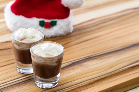 shooters: holiday shooters chocolate and peppermint on a wooden background with a red santa hat
