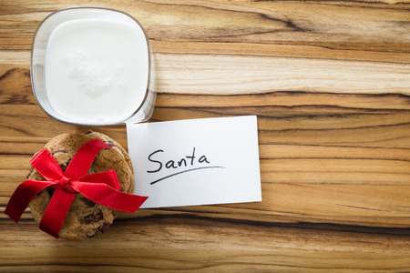 classic santa: view form a above at a stack of cookies and a glass with milk with a   white note for santa