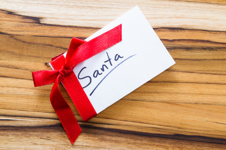 the admirer: view form a hove of a blank note with a red ribbon and a bow for a gift for Santa  concept