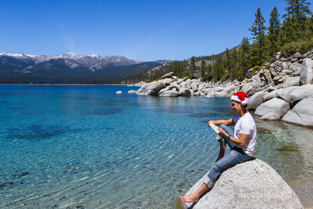 clear day in winter time: Adult male wearing a santa hat relaxing reading a book in Lake Tahoe