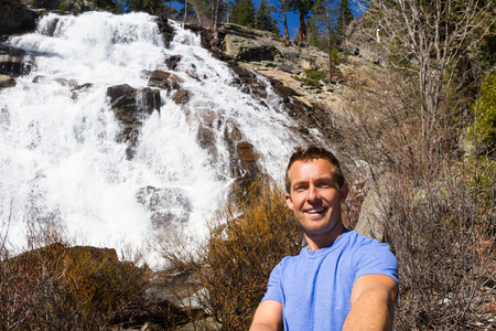 eagle falls: young man taking a self portrait or selfie with Eagle Falls in the background