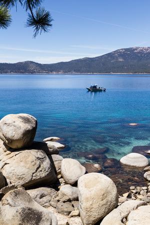 tahoe: fishing boat trolling in Lake Tahoe, clear blue water reflecting the blue sky
