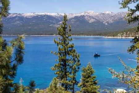 trolling: curric�n barco de pesca en el lago Tahoe, agua azul clara que refleja el cielo azul Foto de archivo