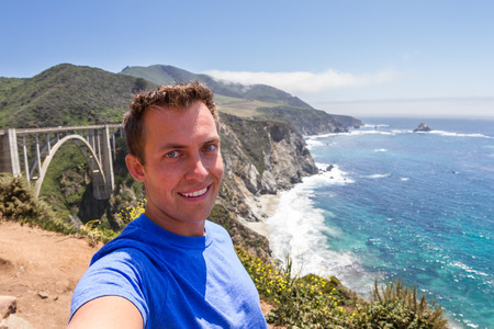 bixby: young man taking a selfie with Bixby bridge and a beautiful coastline in California