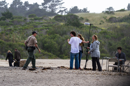 Carmel by the sea, California - May 06 : Park ranger checking on a group of students filming on the beach, May 06 2015 Carmel by the sea, California.