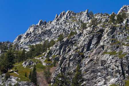 sierras: View of a mountain in springtime with fresh green grass and large sharps rocks in California