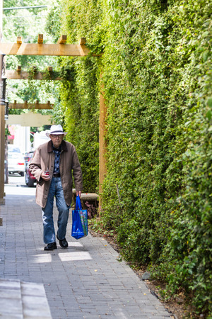 an ally: Calistoga, California - May 08 : Elderly gentleman walking down an ally with a shopping bag and drinking a can of soup thru a straw, May 08 2015 Calistoga, California.