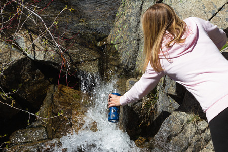 young woman filling her bottle with natural spring water flowing over rocks