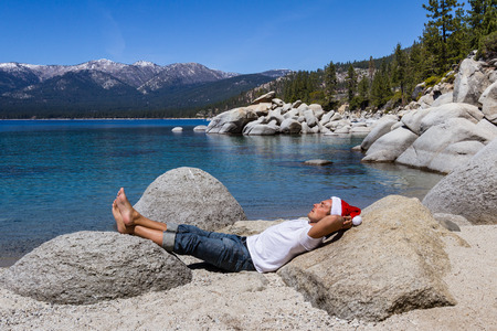 clear day in winter time: Adult male wearing a santa hat relaxing in Lake Tahoe Stock Photo