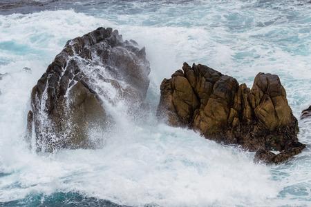 california coast: close up of the drama on the California coast with powerful waves splashing on large rocks Stock Photo