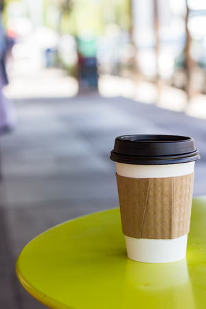 sleeve: paper cup with a lid holding a hot beverage on a side walk table