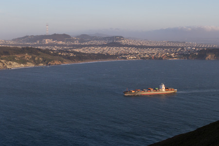 the entering: Large shipping container entering the Bay Area at sun set Stock Photo