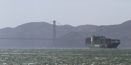 famous industries: San Francisco, California - May 11 : Shipping barge stacked with containers entering the Bay area, May 11 2015 San Francisco, California.