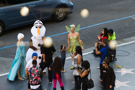 tinker bell: Hollywood Blvd, LA, California - February 08 : People dressed as the Character of Frozen Elsa and Olaf posing with tourist for a tip, February 08 2015 in Hollywood Blvd, LA, California.