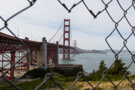 linked: view of the Golden Gate Bridge thru a hole in a chain linked fence