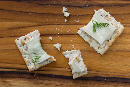 overs: close up of slices of brie cheese on everything crackers with fresh dill Stock Photo