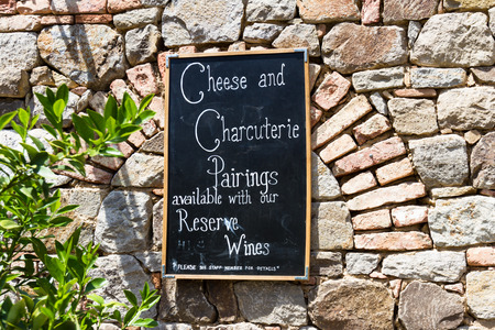 charcutería: un tablero negro en una pared de ladrillo que ofrece quesos y embutidos con vino Foto de archivo