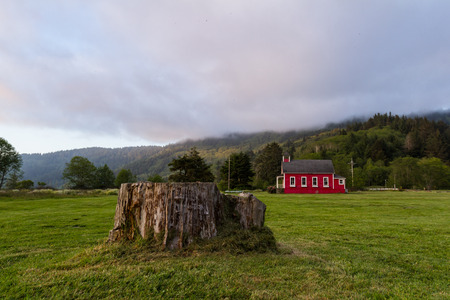 school house: little red school house in a green meadow of northern California
