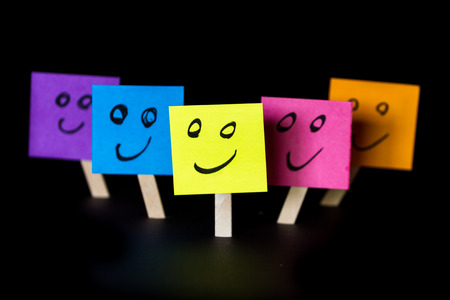 sticky notes with happy faces isolated on a black background for a happy team concept