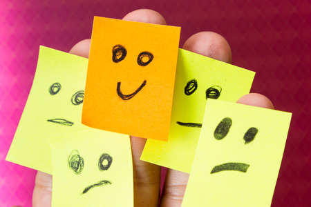 people attitude: concept for optimism with paper faces on multiple fingers one with a happy good attitude Stock Photo