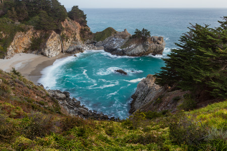julia pfeiffer burns: Waterfall in Julia Pfeifer Burns State Park at sunset with a soft golden color on the rocks