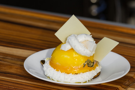 beautiful passion fruit dessert with a coconut marshmallow garnish and white chocolate squares