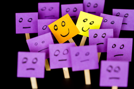 Concept for being different and being happy in a word of normal, hand drawn faces on sticky notes over a black background