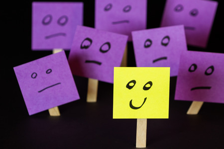 way out: hand drawn faces on sticky notes with on that stands out in a positive way