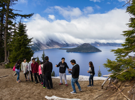 crater lake: Crater Lake, Oregon - May 23 : Tourist taking pictures and posing for photos with the lake and fog in the background, May 23 2015 Crater Lake, Oregon.