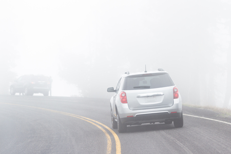 view of a car driving on a paved road with extremely limited visibility due to heavy fog
