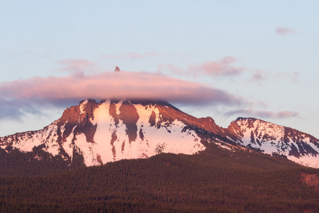 lingering: Mount Thielsen at sunset with a reddish glow and a  lingering fog around the tip of the mountain