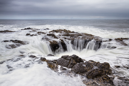 water feature: Thors Well, a feature in the Oregon coast where the water seems to drain down a lava rock sinkhole Stock Photo
