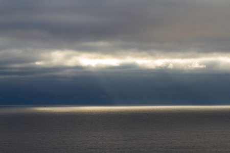 penetrated: tranquil seascape of the pacific ocean in central Oregon with dark clouds and fog being penetrated by bright sun rays Stock Photo