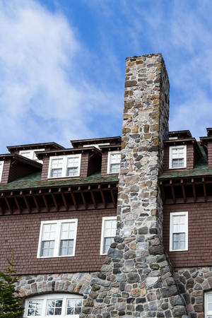 outdoor view of a lodge with many windows and a large chimney Stock Photo