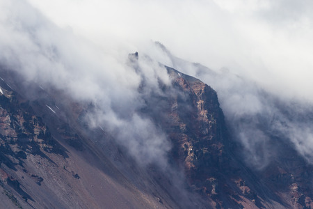 lingering: changing temperatures in spring cause a dense fog to creep over the rim and into the crater in Crater Lake Oregon