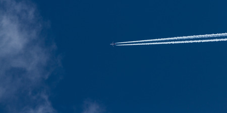toxicity: airplane leaving a dense white trail over a beautiful blue sky