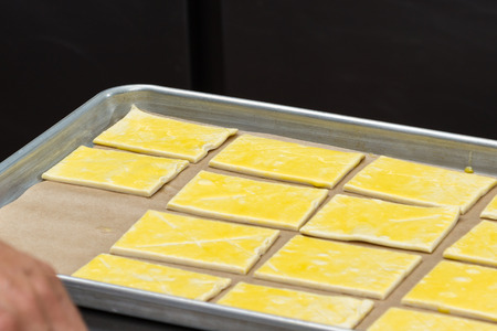 by placing: close up of a chefs hands placing prepared puff pastry on a tray for baking