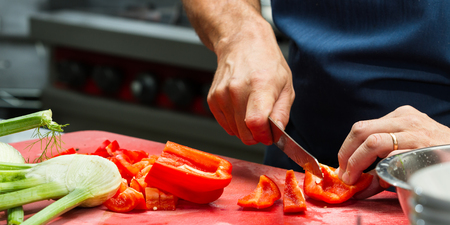 prep: close up of a chefs hands slicing fresh vegetables in a restaurant