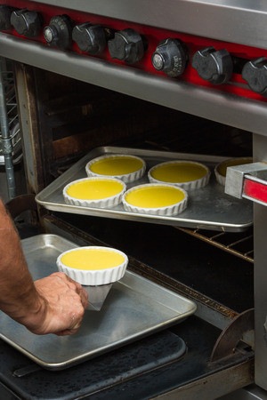 poach: close up of a tray of individual servings of creme brulee preparing in an oven