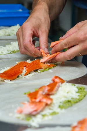 prep: executive chef placing smoked salmon pieces on top of cheese and pesto on thin round shells for dinner service