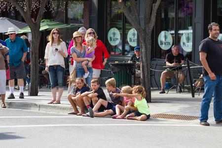 alene: Coeur d Alene, Idaho - June 12 : children sitting on the sidewalk and parents behind them waiting for the parade, June 12 2015 in Coeur d Alene, Idaho