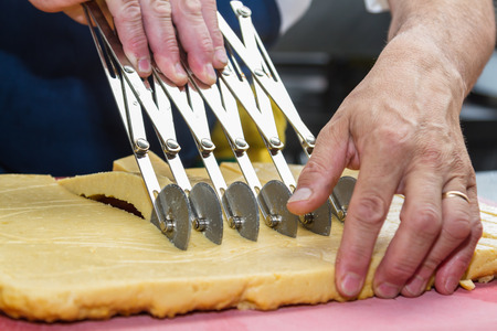 special individual: close up of a chefs hands slicing equal individual servings of panisses with a special cutting tool