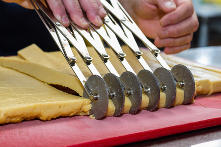 prep: close up of a chefs hands slicing equal individual servings of panisses with a special cutting tool