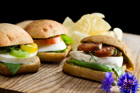sliders: fresh mozzarella and tomato sandwich with fresh basil served with potato chips