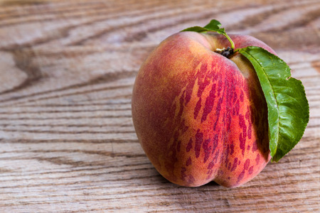 close up of a freshly picked peach on and old wooden table Stock Photo
