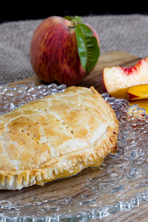sourced: home made peach turnover served with slices of a fresh peach