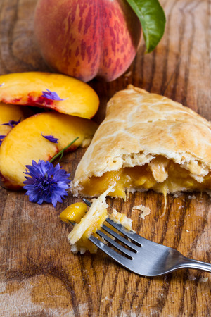 sourced: home made peach turnover served on a wooden serving tray with fresh peach slices Stock Photo