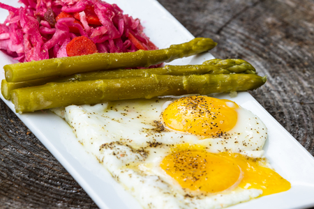 light breakfast: light breakfast consisting on two fried eggs served with fermented cabbage and asparagus