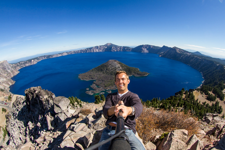 self discovery: young man taking a self portrait with Crater Lake in the background Stock Photo