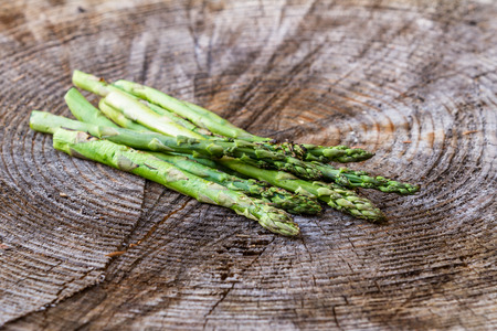 sourced: close up of a bunch of grilled asparagus served on a rustic wooden tree round